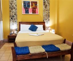 The queen size bed in the Yellow room in La Gargola guesthouse in Old Havana, Cuba